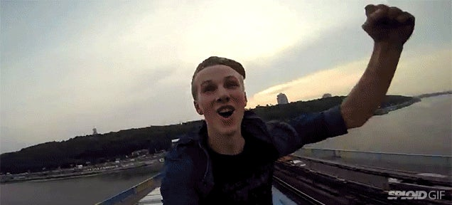Daredevil kid rides a train while on top of the roof of the train