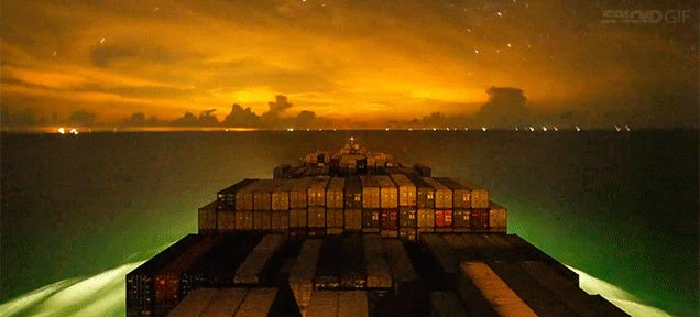 A container ship travelling around the ocean at night is one of the most beautiful things