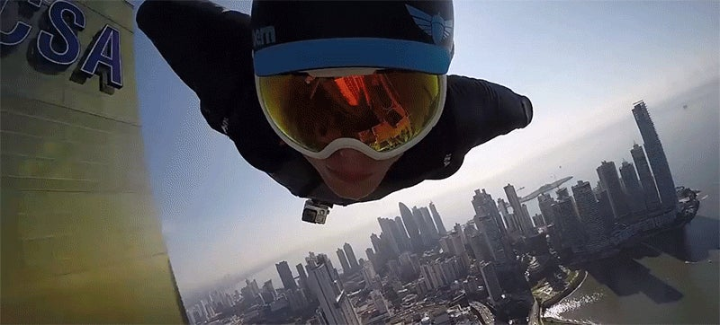 Watch crazy guys in wingsuits fly right next to the face of city buildings