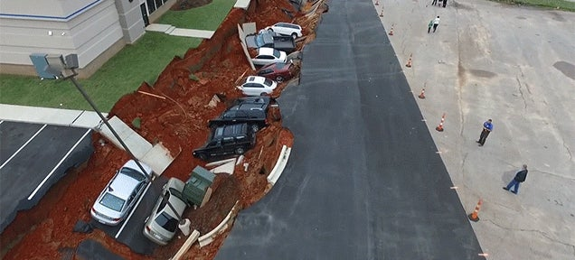 Crazy drone footage of a sinkhole that swallowed cars looks like a disaster movie