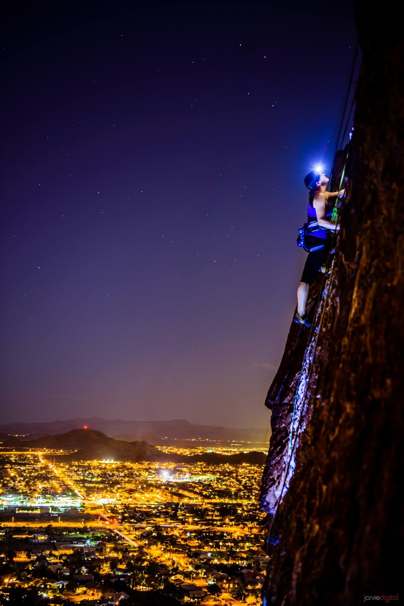 Spectacular photo of a woman climbing a vertical rock wall at night