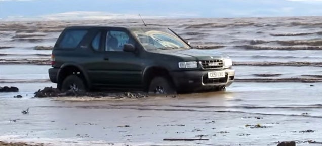 Guy parks on the beach and his car ends up swallowed by the tide