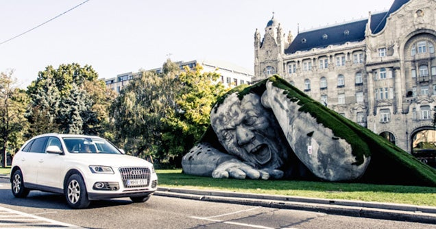 Scary giant man crawls out from the ground in shocking outdoor sculpture