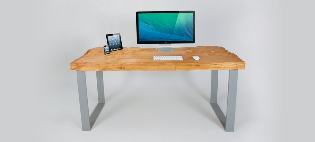 This Undulating Desk Top Has Specially Carved Crevices For Your Tech