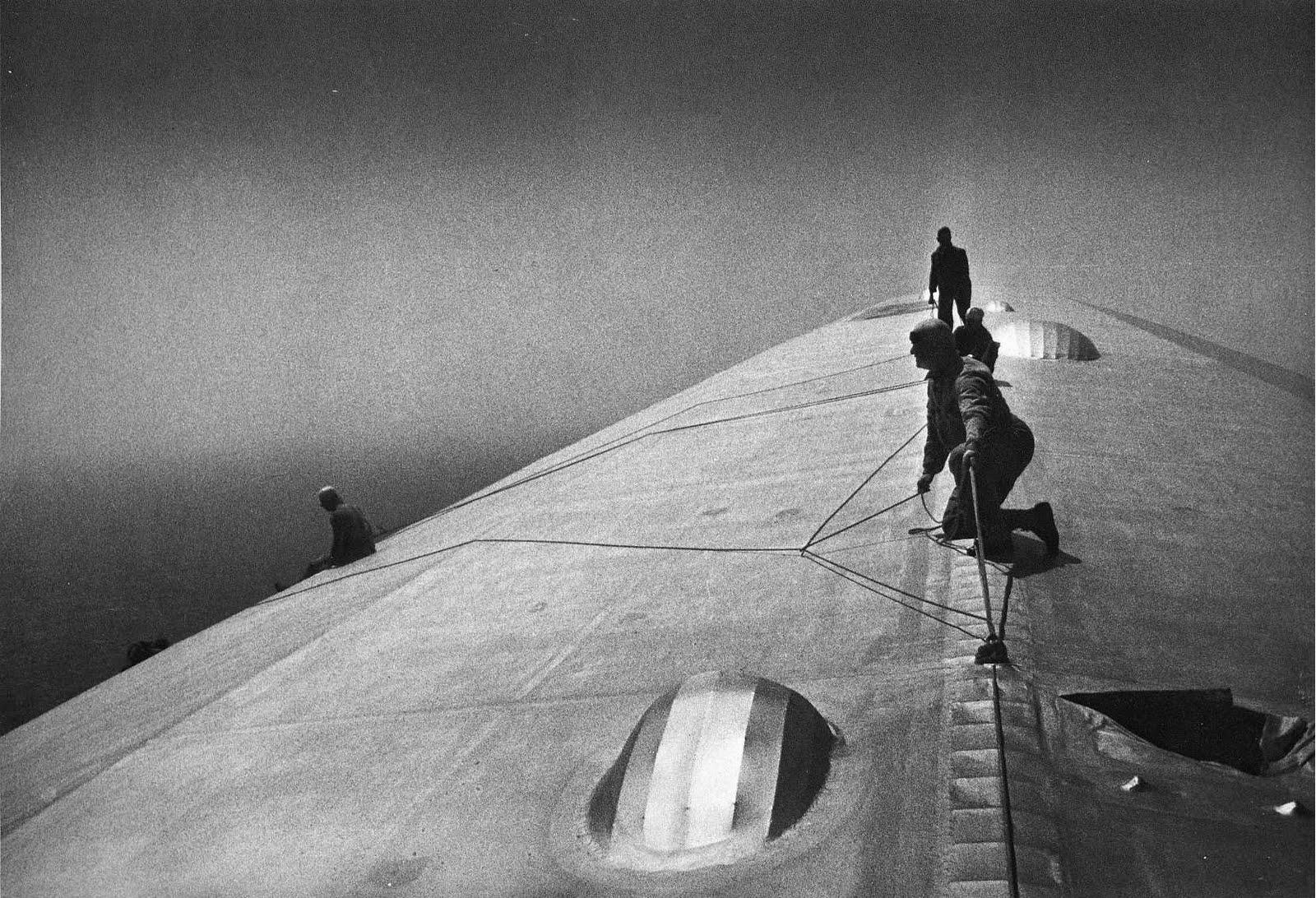 Men fixing a zeppelin in mid-flight over the Atlantic