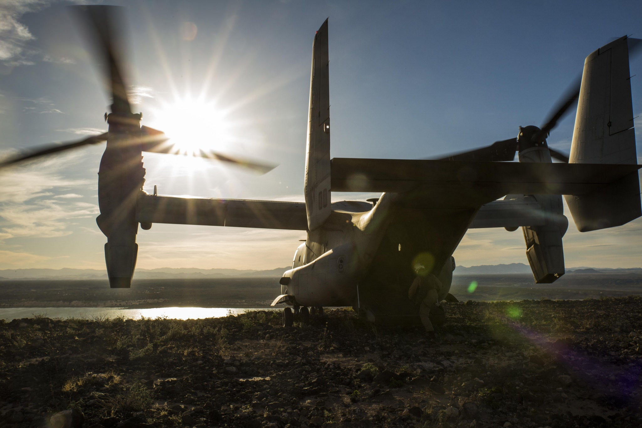 Peaceful Shot Of MV-22 Osprey Overlooking The Sun On Top A Mountain