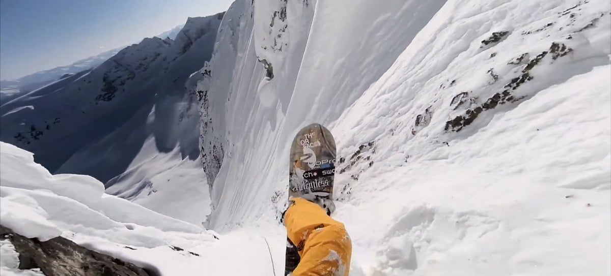 Insane guy rappels down a vertical rock wall to snowboard at hyperspeed