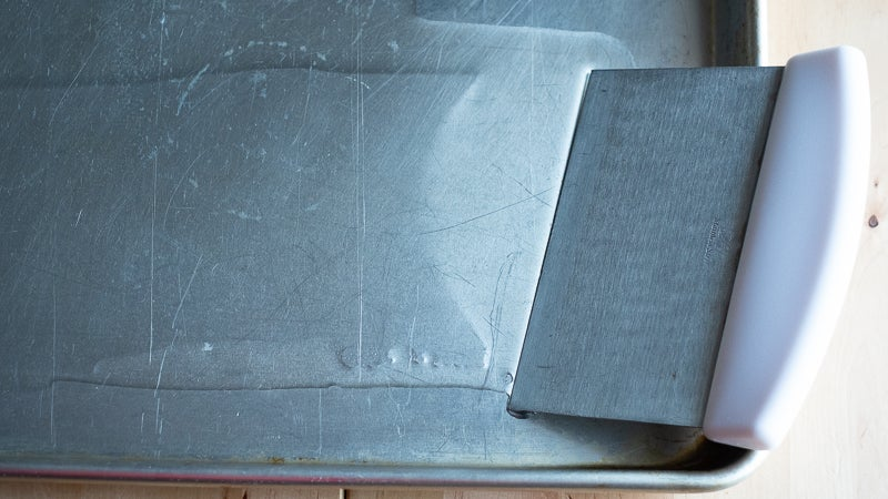 Use A Bench Scraper To Evenly Oil Sheet Pans