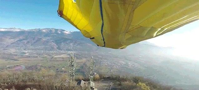 Man in Wingsuit Flies Through a Narrow Opening Between Two Antennas