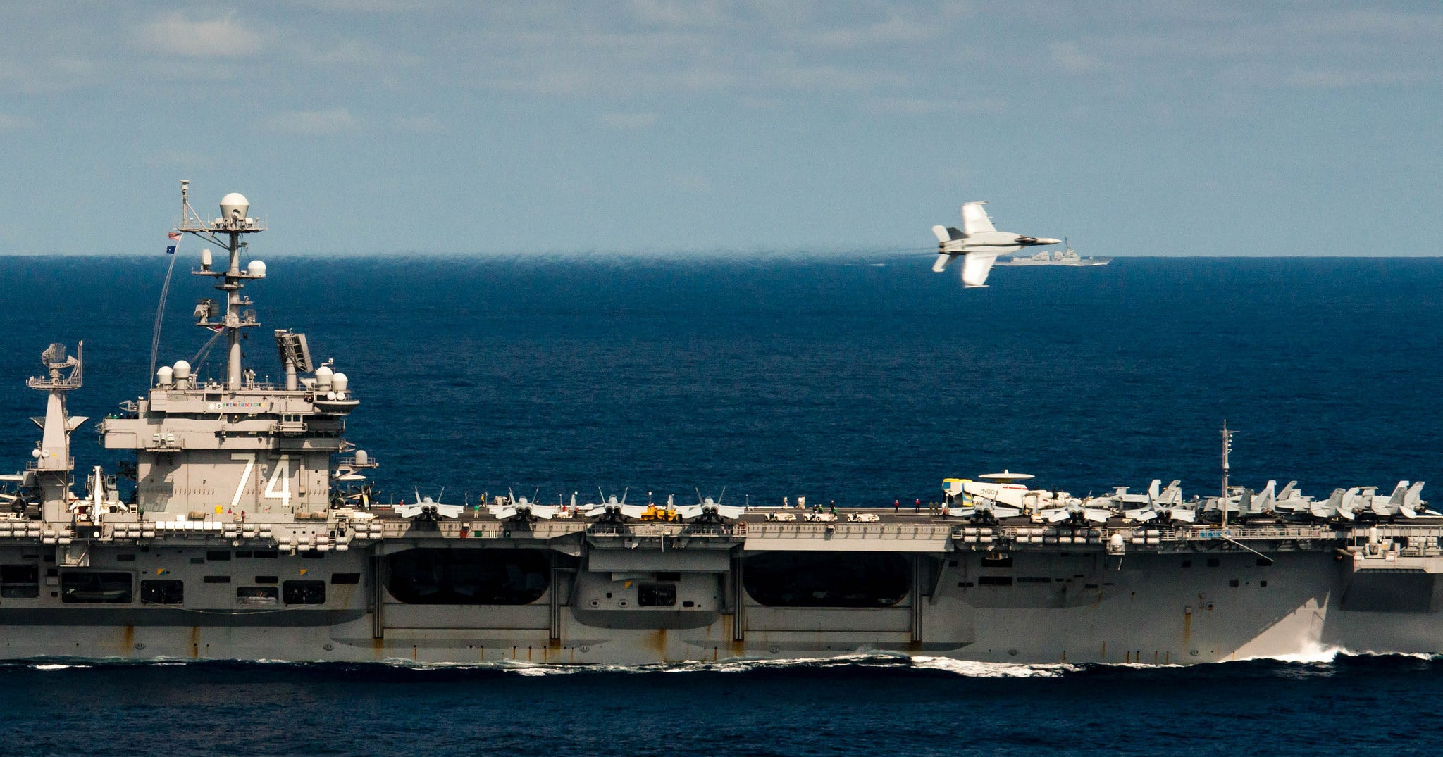 Cool Photo of a F-18 Flyby of an Aircraft Carrier