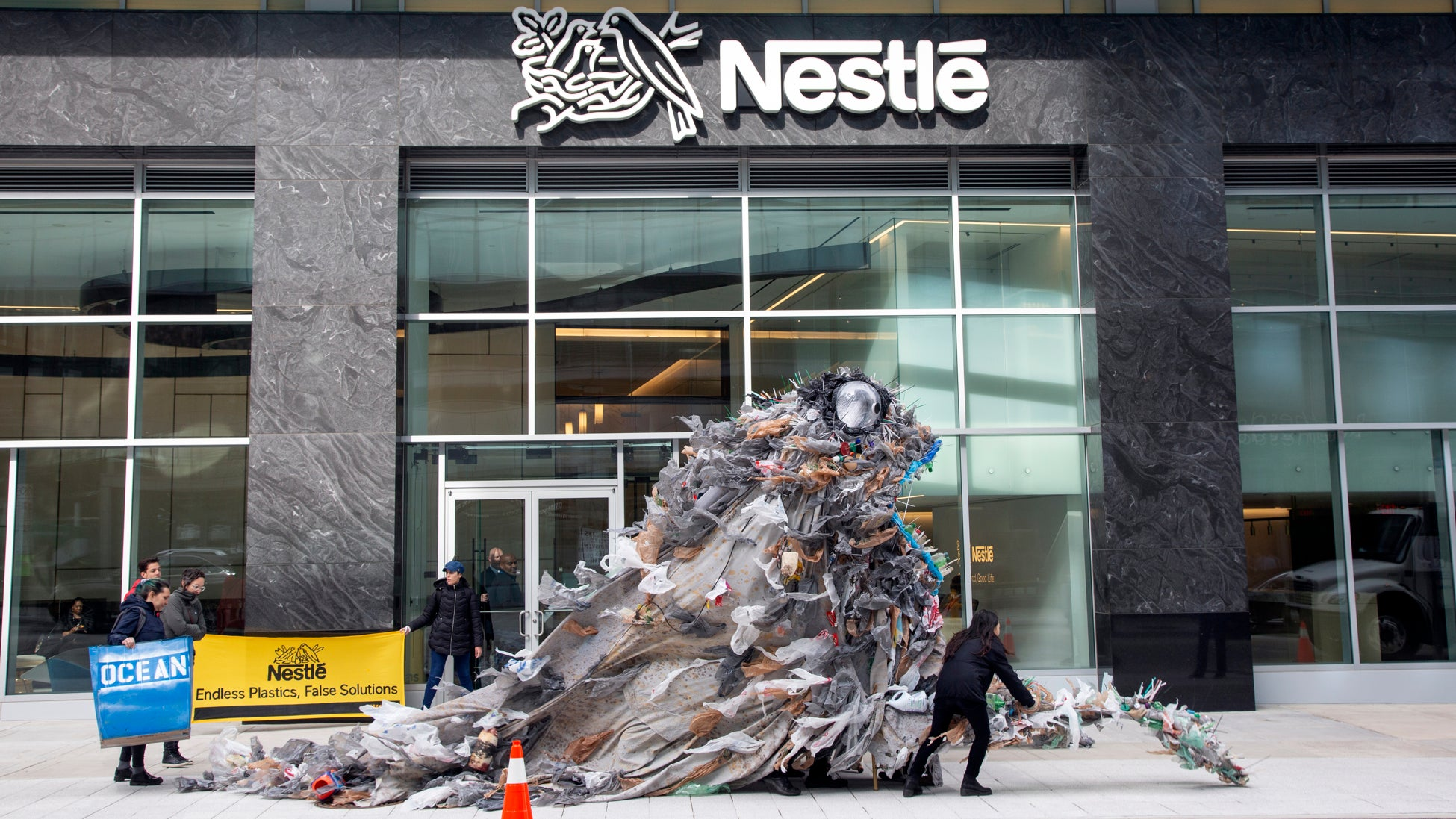 Activists Deliver Giant Trash Monsters To Nestlé Headquarters To Protest Plastic Pollution